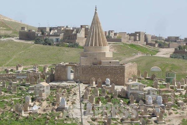 ヤズディ教徒にとって重要なのがクッブと呼ばれる聖塔。三角錐の建物で、ヤズディの村や町には必ずある。内部には聖者や名士が祀られていて、聖墳としての役割も持つ。塔のまわりをとり囲むように墓石が並ぶ。(バシカ・2004年)