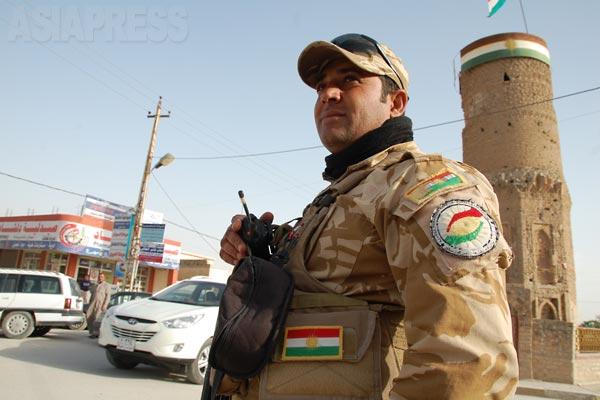 シンジャルはニナワ県にあたるが、クルド系ヤズディ教徒住民がほとんどを占めるため、クルディスタン地域政府がペシュメルガ兵士を派遣し、治安警備を担っていた。市内中心部で。背後にある歴史的建造物の塔は、その後、イスラム国によって爆破された。(シンジャル・2011年)