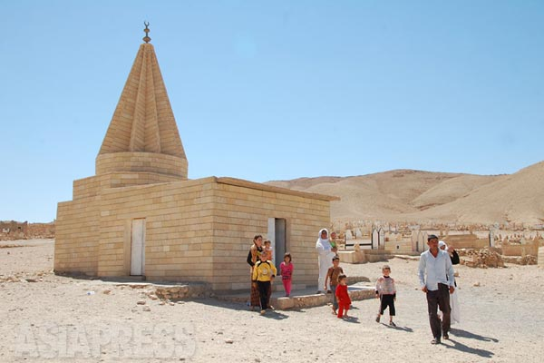 ニナワ県シンジャル山付近。ヤズディ教徒の聖塔クッブと呼ばれる三角錐の建物。周りに墓石が広がる。(2012年)