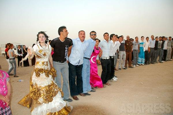 結婚式は親族だけでなく、地区から数百人もの人びとが参加する。軽快な音楽にあわせ、手をつなぎ、踊る。(2012年)