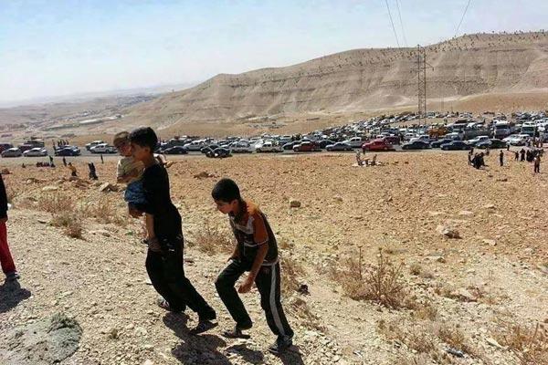 大混乱に陥り、家を捨て、車や徒歩で逃げるヤズディ教徒たち。山に逃れた住民は5万といわれる。(8月3日、地元住民が携帯電話にて撮影)