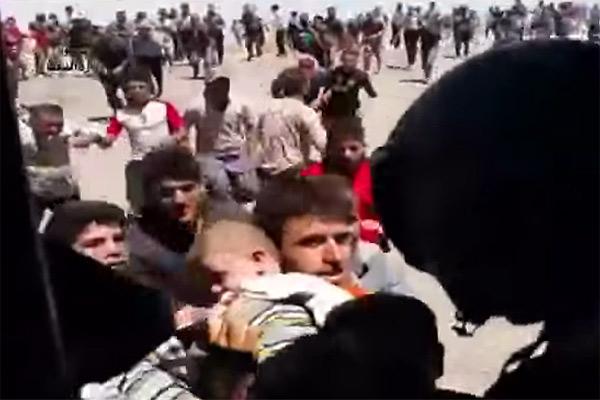 山に包囲され、食糧を絶たれた数万の住民。衰弱死する子どもや老人があいつぐなか、イラク政府軍に続き、アメリカ軍、イギリス軍などの輸送機が食料を投下。乳幼児や病人などの一部住民はイラク軍ヘリで救出されたものの大半は山に取り残された。写真は乳児を救出するイラク軍。(イラク国防省公表映像)