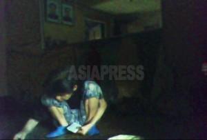 81歳だという日本人女性。トランプ占いに没頭していた。部屋の中に金日成―金正日の肖像画がかかっている。2010年6月平安南道 撮影 キム・ドンチョル(アジアプレス)