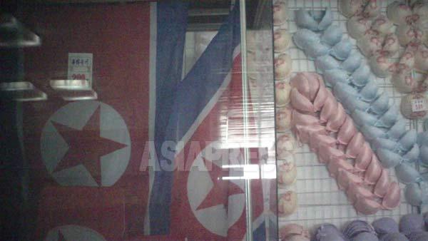 北朝鮮国旗と並んで陳列されたブラジャー。価格表には国旗200ウォン、ブラジャー300ウォンとある。2011年8月、ク・グァンホ撮影