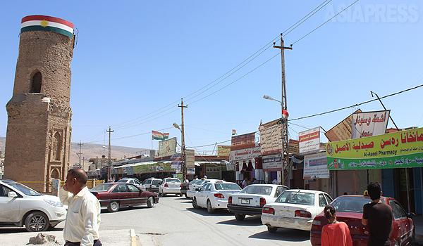 イスラム国が襲撃する1か月半前のシンジャル(クルド名シェンガル)の中心部。クルディスタンの旗が見える。クルディスタン地域政府からは100キロ以上離れた行政管轄外の場所だが、クルド系住民が多いことから地域政府がクルド兵ペシュメルガを派遣するなどして防衛していた。8月、イスラム国の攻勢に治安部隊は撤退し、町は陥落した。(6月中旬・ハッサン・オメル撮影)