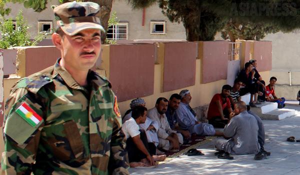 シンジャル地域はクルディスタン地域政府が治安警備を担い、周辺のニナワ県一帯はイラク政府軍が管轄していた。写真は町の警備をしていた治安部隊。後に座り込んでいるのは、近郊から避難していたトルコ系の住民など。イスラム国の侵攻で治安部隊とイラク政府軍が敗走したため、シンジャル地域の住民は取り残される形となった。(6月中旬・ハッサン・オメル撮影)