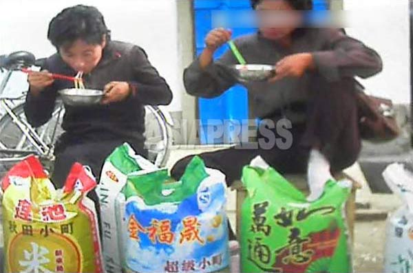 中国産のコメを売る女性たちがソバで腹ごしらえしている。コメの袋には「秋田小町」の商標が。2013年10月北部国境都市。(撮影アジアプレス)