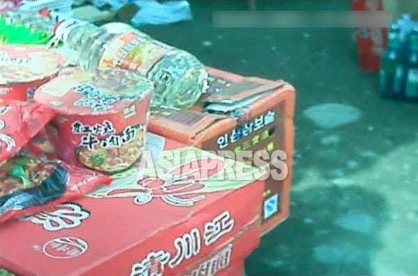 中国製のラーメンとともに、ハングルで「人参三宝酒」と書かれた中国産の酒が見える。2013年10月北部国境都市。(撮影アジアプレス)