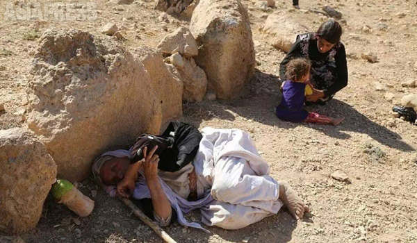 8月3日、イスラム国はシンジャル山周辺地域を制圧。シンジャル山は土漠地帯に伸びる60キロにわたる長大な岩山で、川も木も少ない。真夏の50度を超える気温のなか、孤立した人びとは飢餓と脱水症状に直面する。写真の老人は、衰弱して力なく横たわっている。(8月、住民が携帯電話で撮影)
