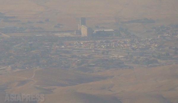 8月、シンジャルに攻め込んだイスラム国。シンジャルの近郊地域も含めると殺戮と迫害から逃れようと脱出した避難民の数は10万におよぶ。一部は安全なクルディスタン地域に逃れたが、幹線道を閉ざされた住民5万の住民は山に逃れた。町も家も失い、ヤズディ教徒が受け継いできたコミュニティーは消滅した。家族が無事に避難できたわけではない。途中で殺害されたり、町に攻め込んだイスラム国によって若い女性が集団で拉致され、イスラム国の戦闘員に戦利品として分配されている。そのほとんどがいまも行方不明のままだ。写真は、シンジャル山の山頂から見下ろした町。いまもイスラム国が支配する。(9月、イラク・ニナワ県シンジャル山・玉本英子撮影)