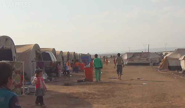 【シリア北東部】 イスラム国に町を襲撃され、シンジャル山に逃げたのち、クルド組織に救出されたヤズディ住民。一部はイラク・クルディスタン地域へと移ったが、シリアでもたくさんの住民が避難生活を送っていた。このネウロズ・キャンプだけでも避難民の数は8000人。シリア政府は地方部では機能しておらず、国連難民高等弁務官事務所(UNHCR)や赤新月社、地元クルド団体などが緊急対応にあたっていた。まもなく厳しい冬がやってくる。(シリア北東部・デレクで 9月・玉本英子撮影)
