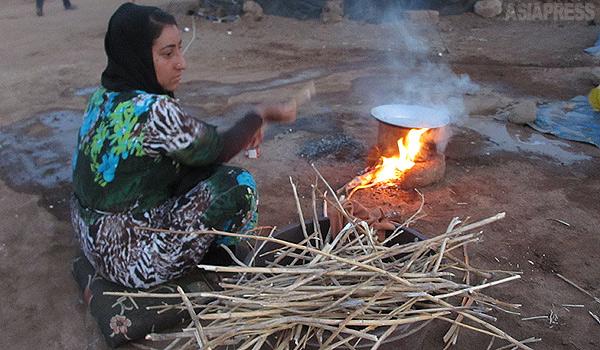 【シリア北東部】 その日の食事を作るだけでも大変だ。ガスやコンロを持っていない人びとは、周辺から木や草を拾い集めてきて、火をおこしていた。(シリア北東部・デレクで 9月・玉本英子撮影)