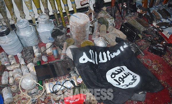 シリア北部の町コバニ(アラブ名:アイン・アル・アラブ)の21日夜の戦闘で、クルド組織、人民防衛隊(YPG)側がイスラム国側から押収した多数の武器。ロケット砲や、爆発物、機関銃など。薬物や注射器は恐怖心を抑えるために戦闘員が使用するという。(22日コバニ市内で撮影・アジアプレス)