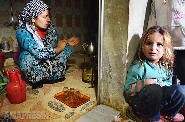 小さなアルコールランプで紅茶を入れてくれるジャミラさん。村の家や畑、家畜もすべて失い、逃げ延びた町でもイスラム国の砲弾にさらされる。(アレッポ県コバニで12月下旬撮影・玉本英子)