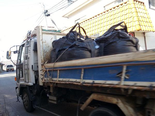 汚染土の詰まった黒い袋「フレコンバッグ」を運ぶトラック(撮影筆者)
