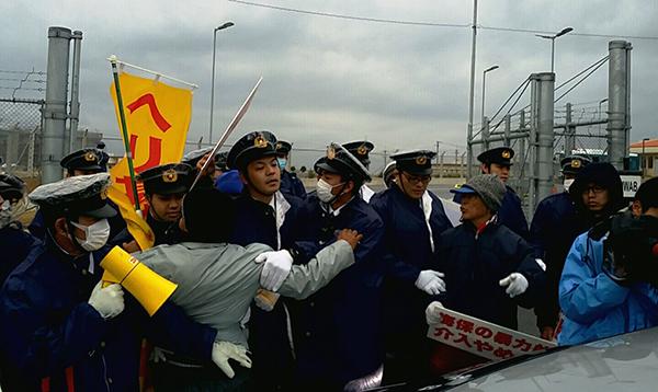 キャンプシュワブのゲート前で海上保安官が乗ったとおぼしき車を止めようとする市民と警察官がもみあいに(撮影・栗原佳子)