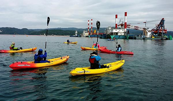 キャンプシュワブ沖にて。海上作業が行われず、海保のボートも出ていない静かな海。陸からの声援にパドルをあげて応えるカヌー隊(撮影・栗原佳子)