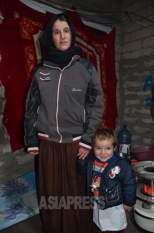 イスラム国に拉致され、脱出したヤズディ教徒のアムシャ・アリさんと息子。コンクリートブロックを積み上げただけの家に親戚と暮らしていた。イラク北部シャリヤで2015年2月玉本撮影。