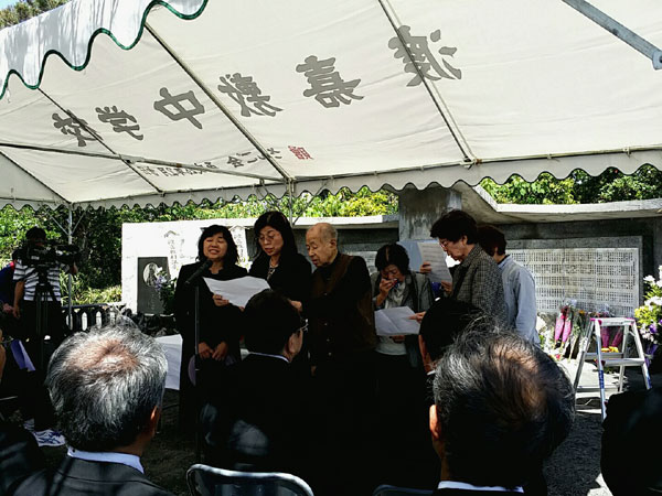 渡嘉敷島の慰霊祭で「命どぅ宝」を歌う宮城千恵さん(左)ら親族。 撮影 栗原佳子