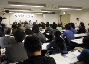 「戦争と報道」シンポジウムの会場でジャーナリストの発言を熱心に聴く参加者。メモを取る参加者も多くいた。 左から石川文洋氏、小林正典氏、高尾具成氏、玉本英子氏、石丸次郎氏=大阪中央区
