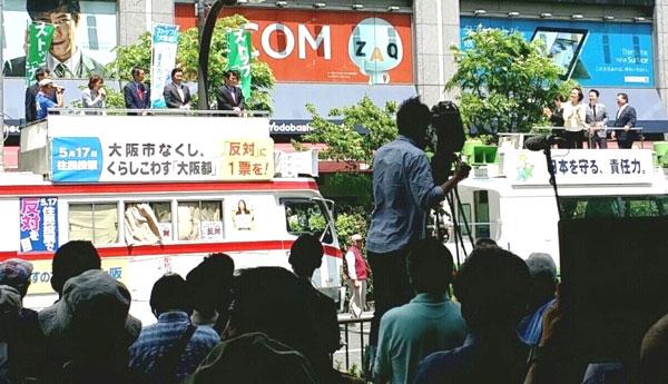 自民党と共産党が宣伝カーを並べ合同で街頭演説会を開催=梅田ヨドバシカメラ前(撮影・栗原佳子)