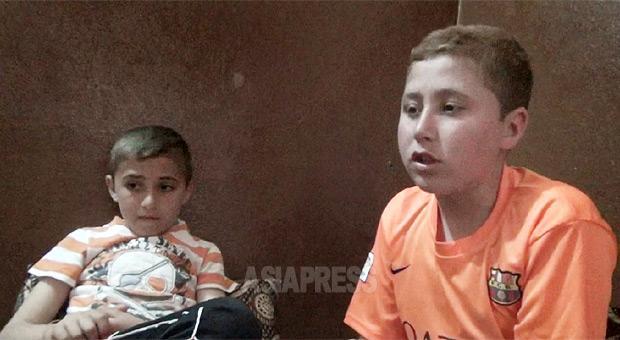 シリア・ラッカの少年軍事訓練所から脱出してきたばかりのヤズディ少年フェルハン君(14歳・写真右)と弟(10歳)。教官に弟と戦うことを命じられ、本気で戦わないと殺すと言われた。彼は素手で戦い、弟の顔を殴り歯を折ってしまった。(イラク北部・4月末撮影:玉本英子)
