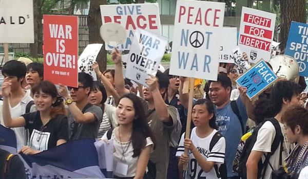 プラカードを持ち、抗議の声を上げる若者たち。ツイッターやフェイスブックでつながった。(大阪ミナミで7月撮影 矢野宏)
