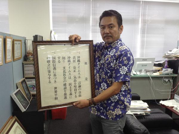 沖縄タイムスの石川次長。手に持つ「社是」には言論の自由、責任公正、気品を堅持する、などとある。(撮影 栗原佳子)