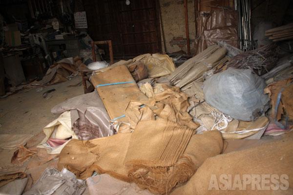 30年以上前に麻袋再生の事業所だった納屋。作業途中の麻袋が散乱している。ここではアスベストの原綿が入っていた麻袋も再生され、当時、作業を行った者たちの中で被害者が出ている