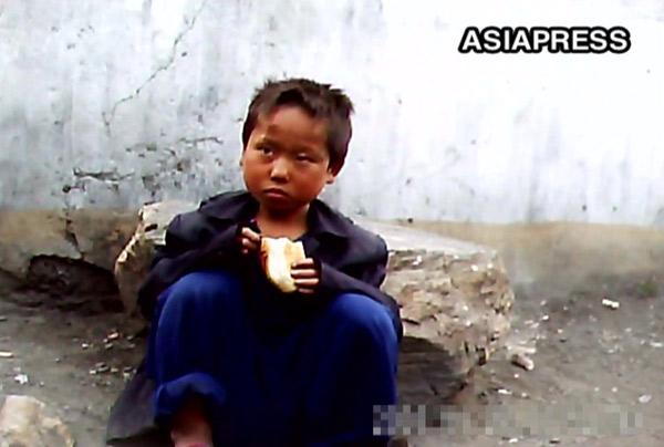 物乞いしたパンを食べている少年路上生活者。2011年6月平壌市のあるアパート街で。撮影ク・グァンホ(アジアプレス)