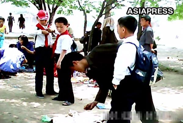 遠足に来た中学生の弁当のおこぼれを拾って食べる若い男性のコチェビ。平壌市の大城(テソン)区域の遊園地の近くで。2011年6月、撮影ク・グァンホ(アジアプレス)