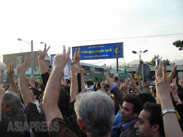 2009年6月15日にテヘランで行なわれた改革派のデモ行進。約50万人が参加。改革派弾圧に大きな役割を果たしたバスィージ(市民動員軍)の施設前でピースを掲げる改革派市民。日没後、一部で騒乱が発生し、改革派側に7人の犠牲者が出た。