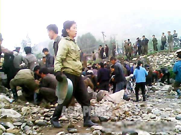 河川整備に動員された住民たちが川原の石を集めさせられている。 2013年6月、北部地方都市で。アジアプレス撮影