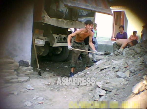 一部の余裕のある住民は、労働動員を「代行」してくれる人を雇って動員ノルマを果たしている。写真の男性は道路のブロック交換作業に動員代行として雇われた人のようである。 2011年8月、平壌市西城区域で。撮影 ク・グァンホ(アジアプレス)