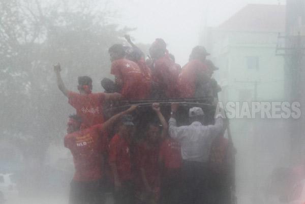 激しい夕立の中でも選挙運動を繰り広げる国民民主連盟(NLD)の運動家たち。(イラワジ地域)
