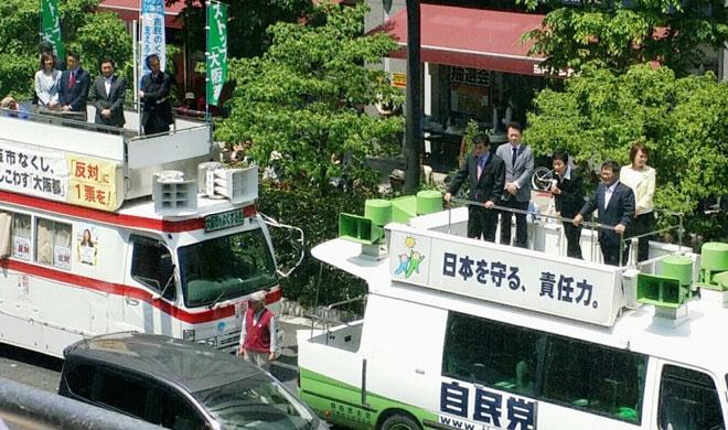 「大阪都構想」の是非を問う今年5月の住民投票では、自民から公明、民主、共産までが反対の立場で連携。街頭では自民党と共産党が宣伝カーを並べてアピールした。(大阪市にて撮影・栗原佳子)