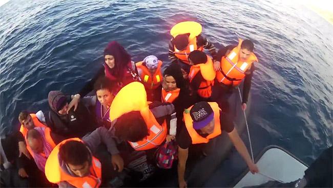 海上でギリシャ沿岸警備隊の警備艇に救助される難民。安物の小さなボートには穴が開いていることも少なくなく、天候次第で波に飲まれて転覆、沈没することもある。(ギリシャ沿岸警備隊撮影映像)