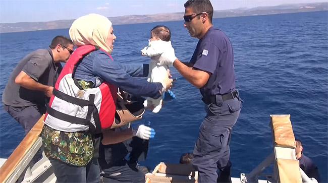 ギリシャ沿岸警備隊に救助された難民親子。「ヨーロッパでの豊かな生活を求めて」という問題ではなく、長引く戦火の中で食料も将来の希望も絶たれ、生きるか死ぬかが突きつけられたなかでの苦渋の選択を強いられた人びとがほとんどだ。イラクで宗派交渉が先鋭化した2005~2008年頃、シリア社会はイラクから数十万人の避難民を受け入れた。ところがシリアが内戦に陥り、多くが難民となると、まるでシリア人が「世界の厄介者」のような扱いを受けてしまう。(ギリシャ沿岸警備隊撮影映像 Λιμενικό Σώμα-Ελληνική Ακτοφυλακή)