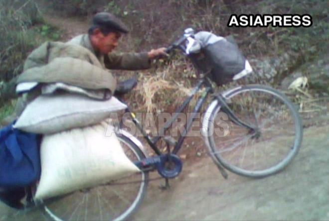 農村から買い出してきた食糧を自転車に載せて運ぶ男性。労多くして実入り少ない仕事であるため都市貧民が多い。2010年10月平安南道 キム・ドンチョル撮影
