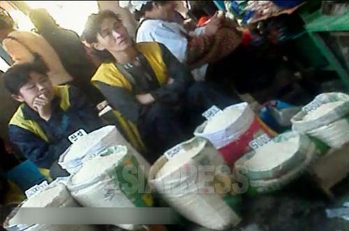 客を待つ女性コメ商人。コメの種類と価格が表示されている。 2012年11月 両江道恵山(ヘサン)市場で、撮影アジアプレス