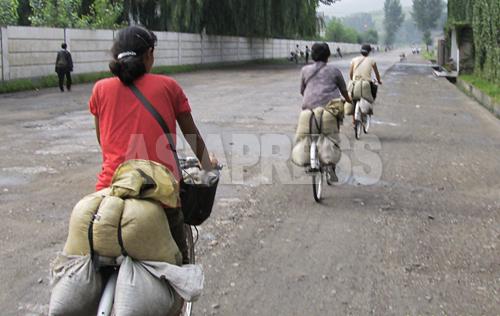 取締りを避けるために裏道を自転車で疾走する「テゴリクン」の女性たち。2008年8月平壌市郊外の農村部で、撮影チャン・ジョンギル(アジアプレス)