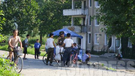 農村で仕入れた穀物を運ぶ途中に、保安員(警察)の取り締まりに引っかかった、夫婦とみられる「テゴリクン」。「間違いなく賄賂を要求される」と撮影者は言った。 2008年8月平壌市郊外の農村部で、撮影チャン・ジョンギル(アジアプレス)