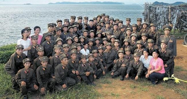 痩せて小さな兵士。西南戦線の島防衛部隊を訪問した金正恩氏の記念撮影。よく見ると兵士たちは、皆幼く非常に痩せている。北朝鮮軍の下級兵士には栄養失調が蔓延している。2012年8月労働新聞より引用。