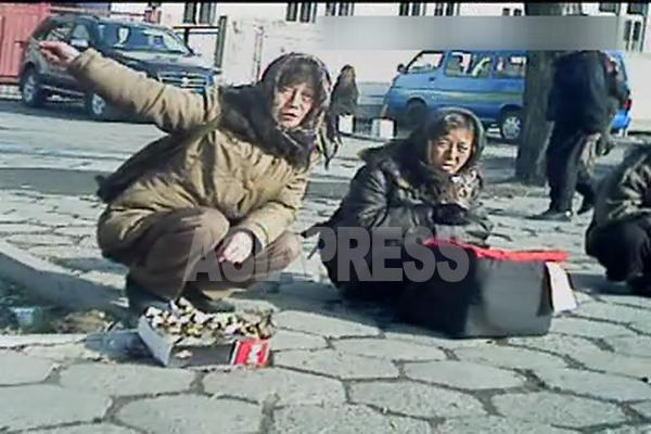 (参考写真)新義州駅前の路上で物売りをする女性。配給のない庶民にもインフレなど制裁の影響必至だと思われるが。2012年11月(アジアプレス)