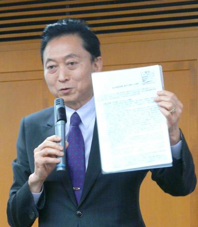大阪市で講演する鳩山元首相。普天間「県外移設」を断念するきっかけとなった問題の文書のコピーを手に語る鳩山さん(撮影・栗原佳子)