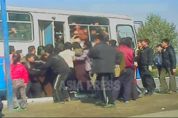 市内バスに乗ろうと殺到する人々。(2012年11月恵山市 リ・フン撮影)】