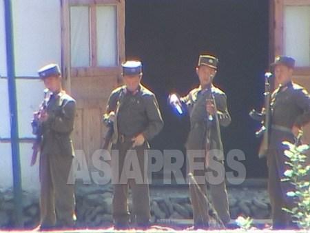 朝中国境は脱北や密輸防止のため厳戒態勢が続いている。写真は巡察前の点検を受ける国境警備兵。2004年8月、朝中国境の川・豆満江上流で中国側から撮影。(アジアプレス)