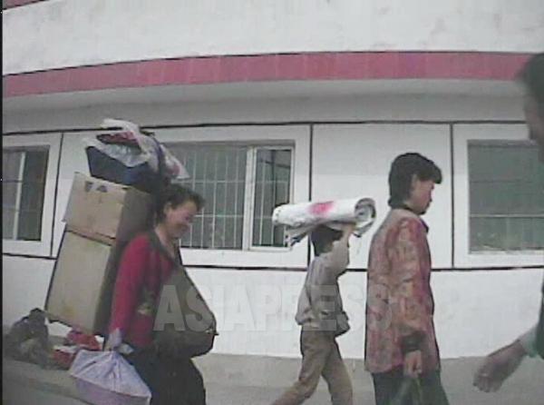 大荷物を背負い、胸にはリュックを抱え、風呂敷包みまで手に持ってい市場に向かう。2008年9月黄海南道東海州市にてシム・ウィチョン撮影(アジアプレス)