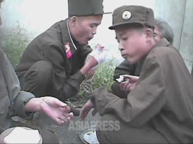 左の兵士が食べているのはおそらく「人造肉ごはん」。油を搾った大豆かすを乾燥させご飯を詰めたもの。2008年9月黄海南道海州市にてシム・ウィチョン撮影(アジアプレス)