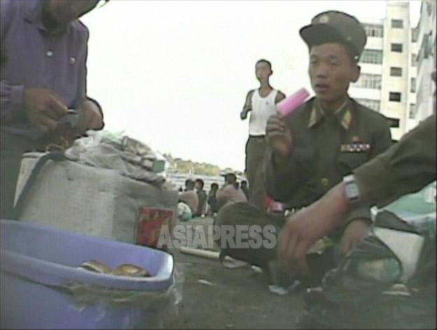 道に座り込んだ兵士が食べているのはアイスキャンデー。冷蔵庫を所有する金持ちが作っ て「売り子」の女性に卸す。2008年9月黄海南道海州市にてシム・ウィチョン撮影(アジアプレス)